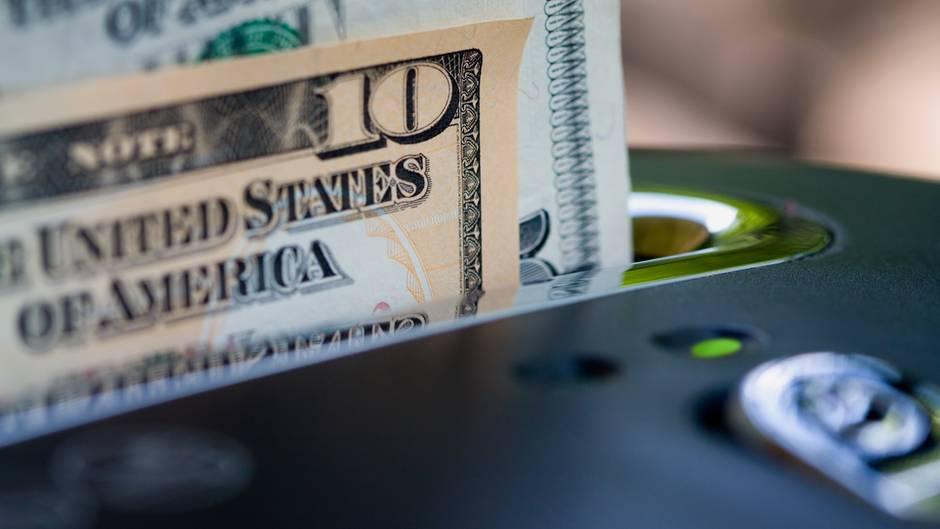 In einem Aktenvernichter stecken Dollar-Noten