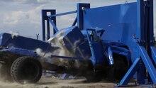 Ein blauer LKW zerschellt in einem Crashtest an einer massiven Stahlwand