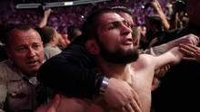 Männer versuchen, MMA-Kämpfer Khabib Nurmagomedow zurückzuhalten, nachdem Nurmagomedow ins Publikum gesprungen ist