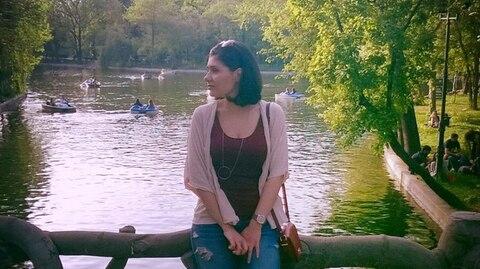 Frau sitzt auf Baumstamm vor See