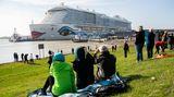 """Viele Sehleuteauf dem Deich: Siebeobachten, wie das Kreuzfahrtschiff """"Aida Nova"""" während der Überführung auf der Ems von Schleppern durch das Ems-Sperrwerk Gandersum manövriert wird."""
