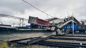 Auf den Trümmern einer Brücke steht ein roter Kieslaster. Die Brückenteile liegen quer über Bahngleise und Güterwaggons