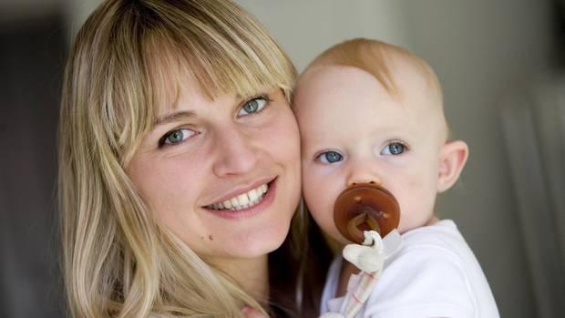Eine junge Mutter mit Baby auf dem Arm