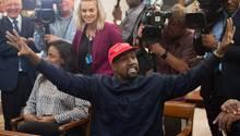 Rapper Kanye West beugt sich über den Schreibtisch von US-Präsident Donald Trump und zeigt ihm ein Foto auf dem Smartphone