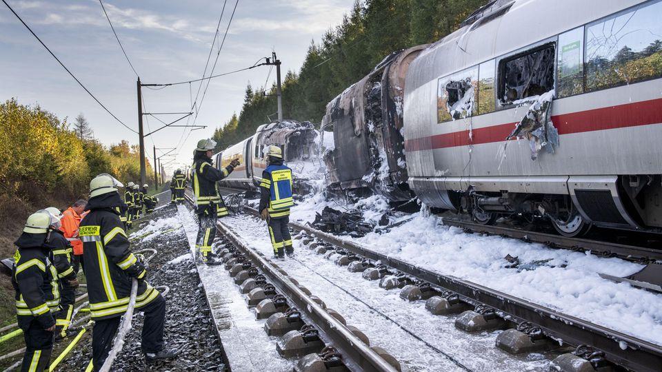 Feuerwehrleute sind nach dem Brand eines ICE auf der Schnellstrecke zwischen Köln und Frankfurt in der Nähe von Montabaur