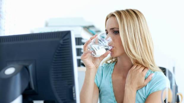 Eine blonde, junge Frau sitzt in einem Büro vor einem Monitor und trinkt dabei aus einem Wasserglas
