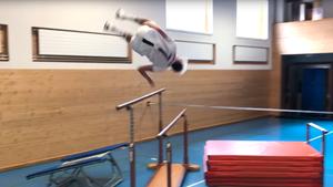 Ein junger Mann in weßem Fußball-Dress schlägt einen Salto über einen Stufenbarren
