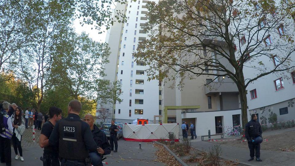 Polizisten vor einem Hochhaus in Berlin, an dem ein Junge von einem herabfliegenden Gegenstand erschlagen wurde