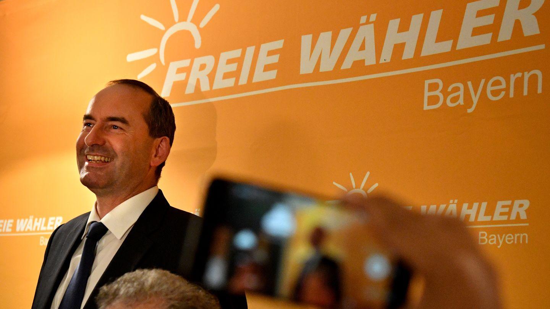 """Vor einer orangen Wand mit weißem Schriftzug """"Freie Wähler Bayern"""" steht ein Mann im Anzug und lächelt breit"""