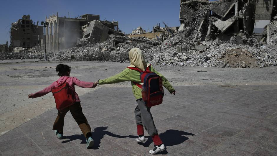 Alltag in Raqqa: Zwei Schülerinnen eilen an den Ruinen ihrer Stadt vorüber