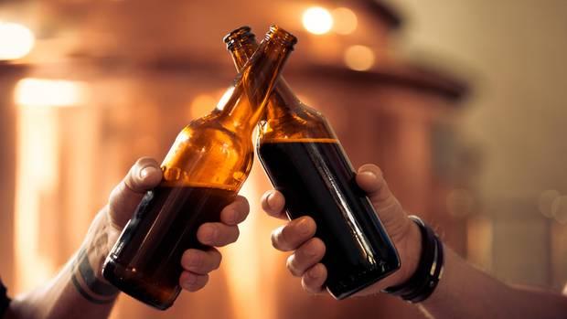 Zwei Männer stoßen mit Bierflaschen an