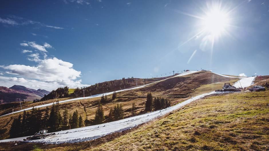 Strahlender Sonnenschein, 20 Grad und eine Pistenraupe auf der Kunstschneepiste: Saisoneröffnung in Kitzbühel.