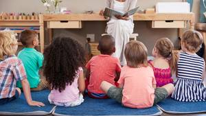 Erzieherin liest Geschichte aus Buch, Kinder sitzen vor ihr