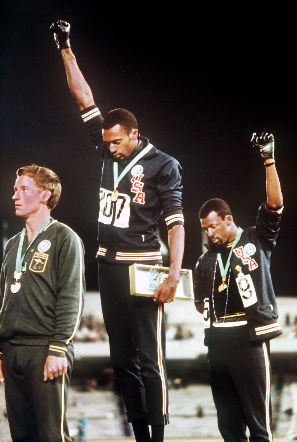 """Tommie Smith (M., Goldmedaille) und John Carlos (r.,Bronzemedaille) mit hochgereckter geballter Faust in schwarzem Handschuh für die """"Black Power""""-Bewegung. Links der Gewinner der Silbermedaille, der Australier Peter Norman."""