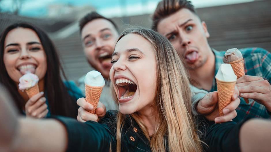 Junge Erwachsene halten Eistüten in den Händen und scherzen für ein Selfie