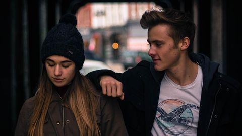 Junger Mann legt einer Frau den Arm um die Schulter