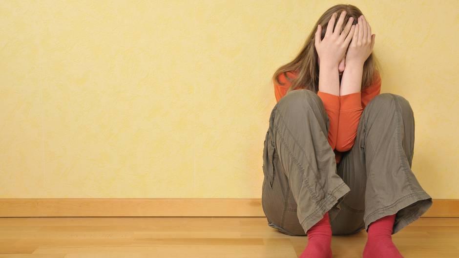 Eine schockierte 14-Jährige kauert am Boden