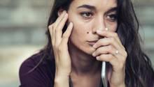 Eine junge Frau hält ihr Smartphone in der Hand