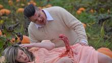 Eine schwangere Frau im rosa Kleid liegt auf dem Rücken, aus ihrem Bauch ragt ein blutiges Alien. Ein Mann beugt sich über sie