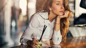 Eine Frau sitzt am Tresen und trinkt einen Cocktail