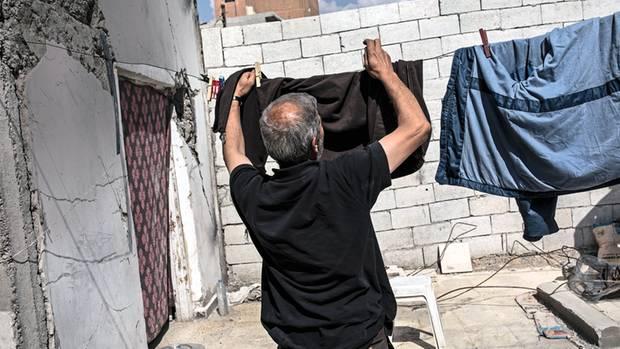 Ahmad Abdullah hängt im Hof seines zerstörten Hauses Wäsche auf