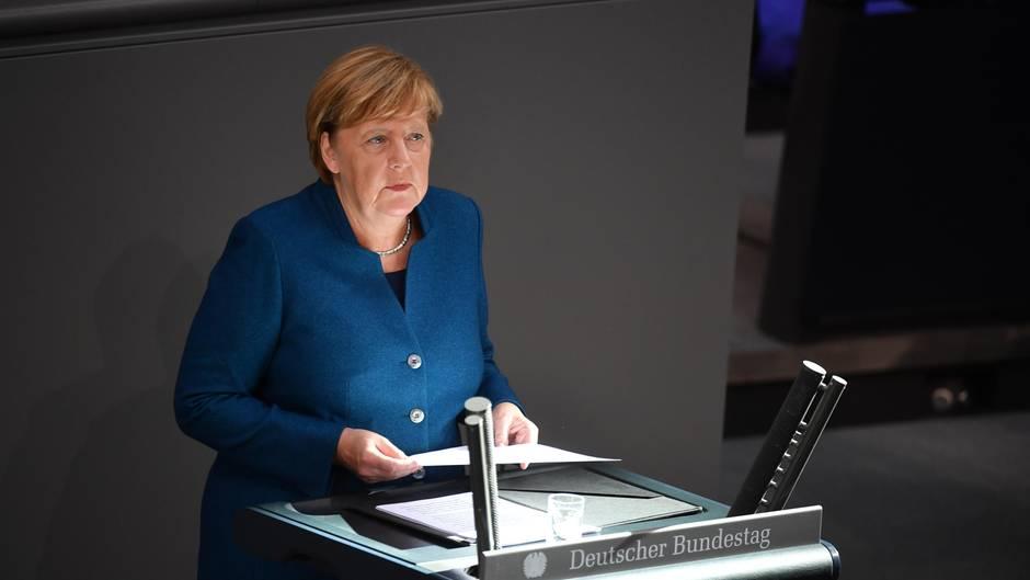 Bundeskanzlerin Angela Merkel steht am Rednerpult des Bundestages, auf das ein Sonnenstrahl trifft