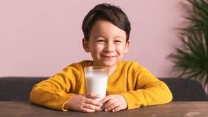 Ein Junge sitzt mit einem Glas Milch am Tisch