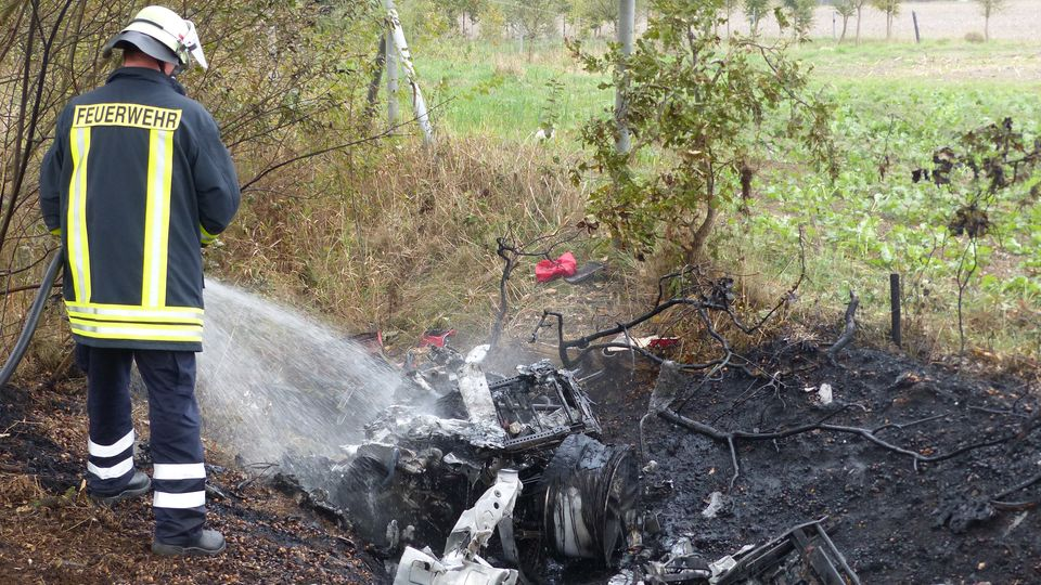 Ein Feuerwehrmann löschtdie Überreste des ausgebrannten Ferraris