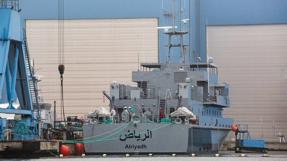 Ein marinegraues Schiff liegt vor einer blauen Werfthalle mit weißen Rolltoren. Am Heck ein arabischer Schriftzug
