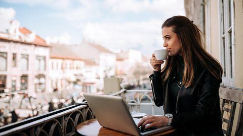 Frau sitzt auf einem Balkon an einem Laptop