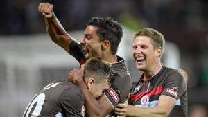 Drei Fußballerspieler in braunen Trikots liegen sich in den Armen. Der Mittlere streckt jubelnd seine Faust in die Luft