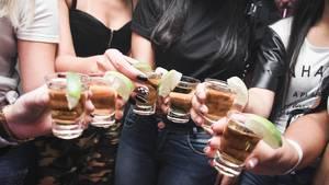 Frauen halten ihre Drinks in die Kamera