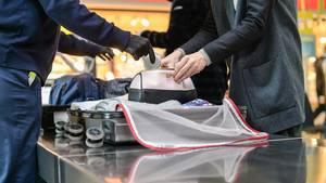 Ein Sicherheitsbeamter kontrolliert das Gepäck einer Reisenden am Flughafen