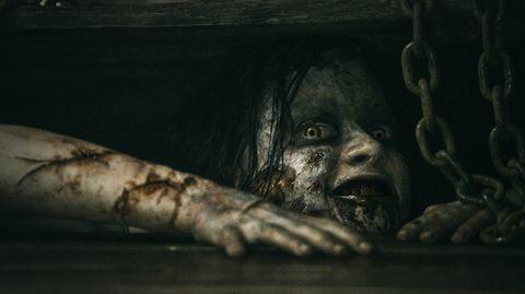 Gruselig aussehende Frau schaut aus einer Bodenluke