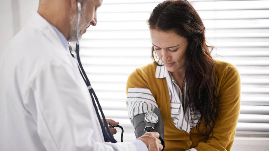 Eine Frau ist beim Arzt und lässt ihren Blutdruck prüfen