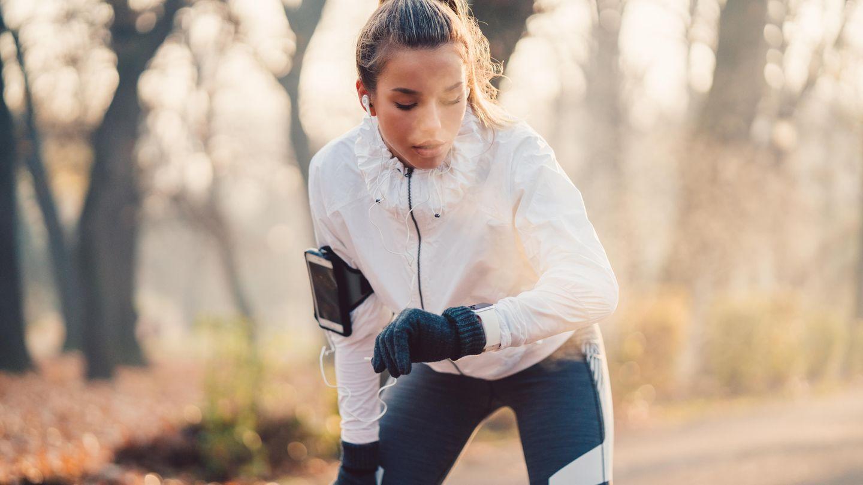 Eine junge Frau joggt durch einen herbstlichen Wald