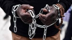 Die Hände eines schwarzen Mannes in Ketten