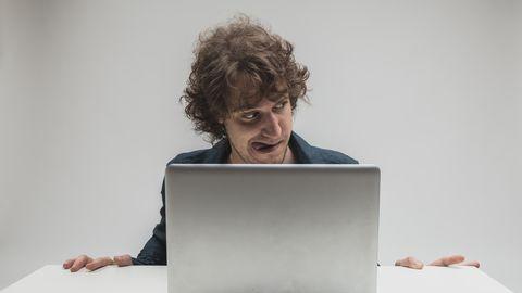 Ein Mann schaut gierigen Blickes Pornos auf seinem Computer