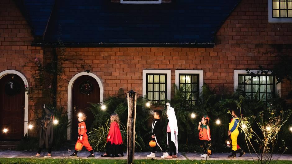 Verkleidete Kinder ziehen an Halloween durch die Straße
