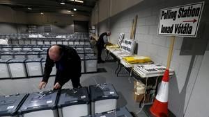 Ein Wahlhelfer bereitet in einer Halle die Wahlurnen vor