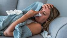 Eine Frau liegt mit Fieber und Erkältung auf dem Sofa