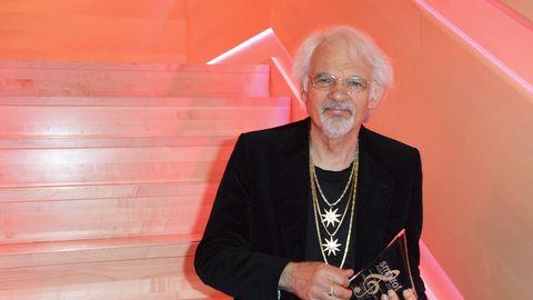 Ingo Interburg, ein Mann mit weißen Haaren und weißem Bart, steht bei einer Preisverleihung mit Trophäe vor einer roten Treppe