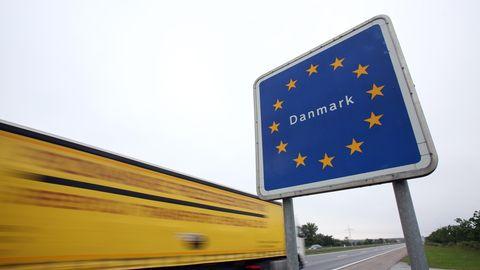 Ein LkW fährt an einem dänischen Grenzschild vorbei