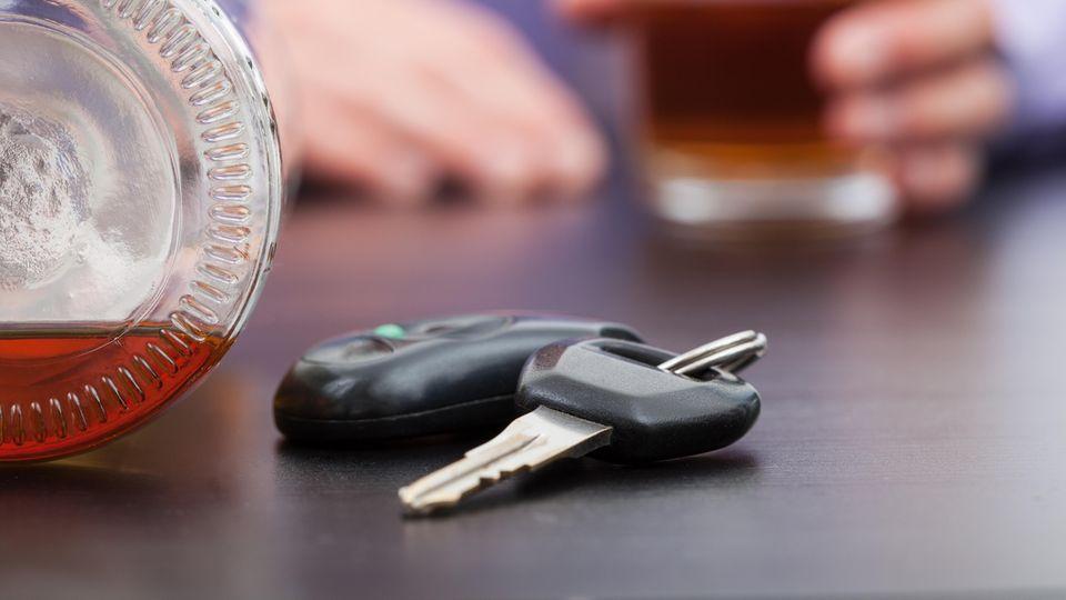 Autoschlüssel und daneben eine Flasche Schnaps