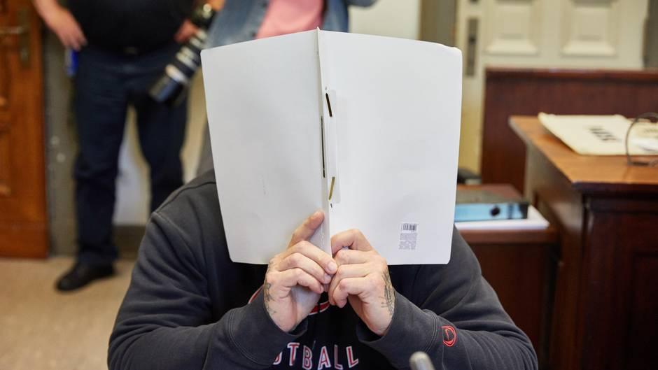 Ein Mann mit tätowierten Händen hält sich im Gerichtssaal einen weißen Schnellhefter vor sein Gesicht