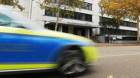 Vor dem Polizeipräsidium Freiburg fährt ein Polizeiauto vorbei. Das Auto ist wegen seiner Geschwindigkeit unscharf zu sehen