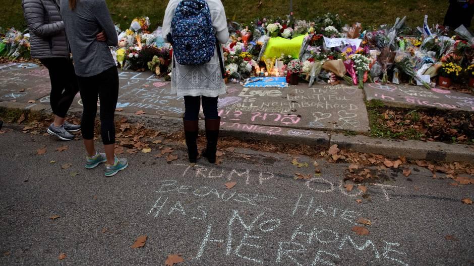 Drei junge Frauen stehen vor einem Meer aus Blumen und Kerzen und trauern um die Opfer von Pittsburgh