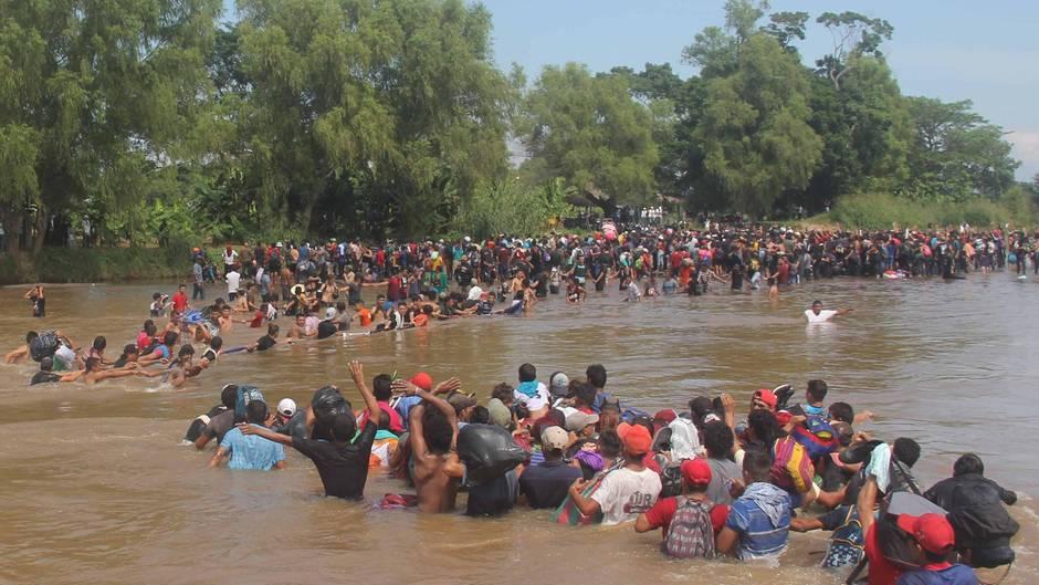 Flüchtlingskarawane: Hunderte Migranten bilden Menschenkette am Grenzfluss und gelangen so nach Mexiko