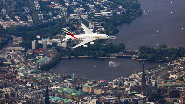 Ein Airbus A380 von Emirates fliegt über die Hamburger Innenstadt und die Alster