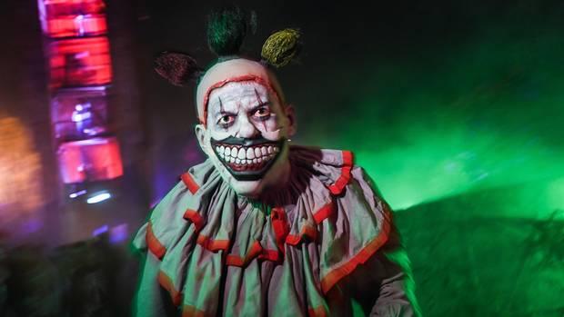 Ein Mann mit einer böse grinsenden Clownsmaske steht vor grün beleuchtetem Nebel